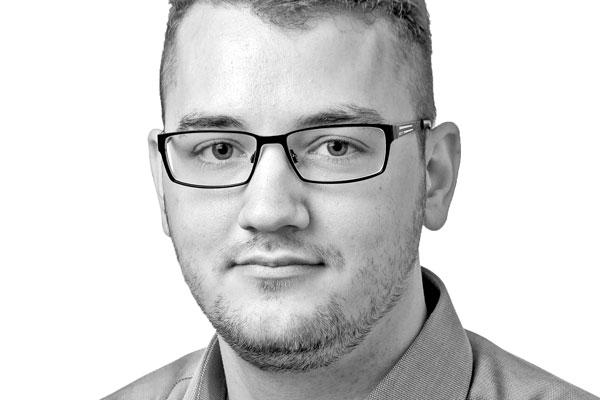 Gesicht eines sympathisch lächelnden jungen Mannes mit kurzen dunklen Haaren und Brille