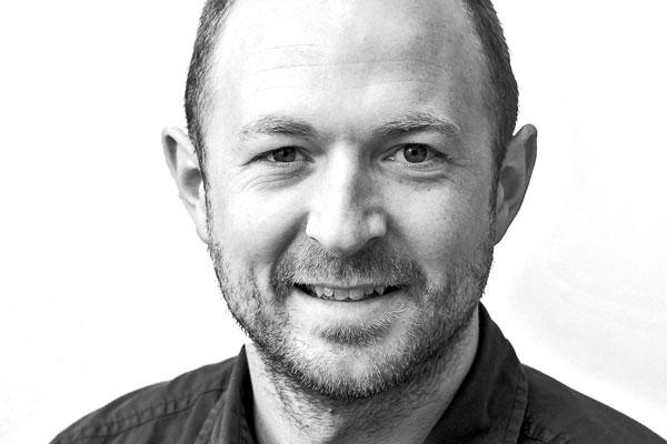 Gesicht eines sympathisch lächelnden Mannes mittleren Alters mit hellen, schütterem Haar und Bart