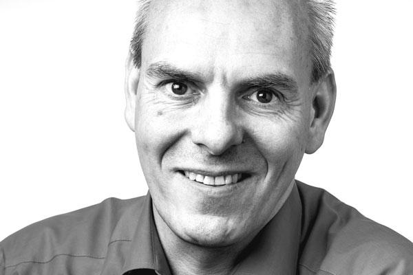 Gesicht eines sympathisch lächelnden Mannes mittleren Alters mit grauem, schütterem Haar