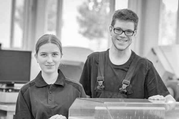 Eine junge Frau und ein junger Mann stehen freundlich lächelnd in der Produktionshalle einer Druckerei