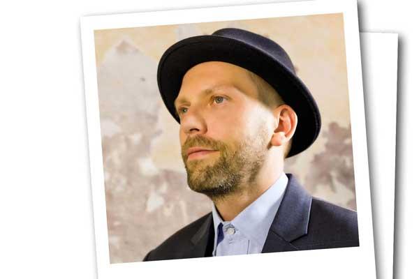 Ein sympathisch lächelnder Mann mittleren Alters mit Hut